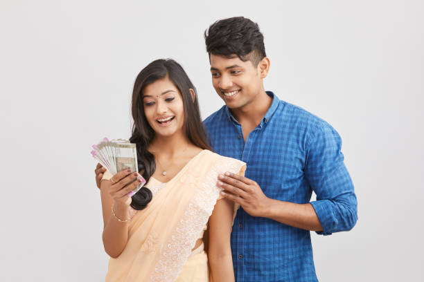 Exited cheerful young couple holding Indian currency on white